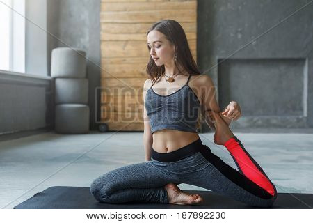 Young woman in yoga class making asana exercises. Girl do mermaid pose, variation of rajakapotasana. Healthy lifestyle in fitness club. Stretching