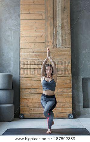 Woman in yoga class making asana exercises. Girl do eagle pose, garudasana. Healthy lifestyle in fitness club. Stretching