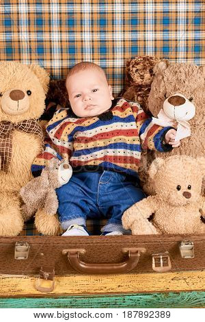Baby, teddy bears and suitcase. Little child with toy animals. Toy safety tips.