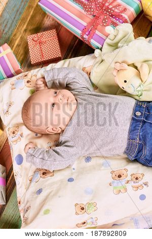 Little kid and gift boxes. Child on pillow, top view. Baby holiday tips.