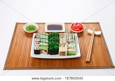 Japanese food restaurant delivery - sushi maki, unagi and roll platter set on mat isolated on white background