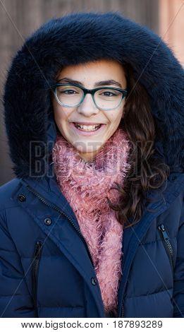 Smiling preteen girl wearing fur hood at winter