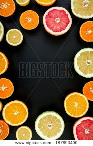 Round frame made of oranges, grapefruit and lemon isolated on black background. Flat lay, top view. Tropical summer mix of fruits