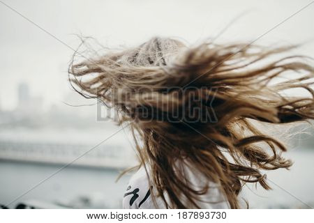 Blond girl shaking the hair in the city.