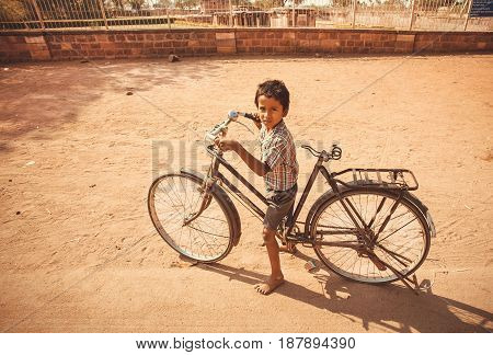 KARNATAKA, INDIA - FEB 9, 2017: Unidentified boy cycling on bicycle outdoor at hot weather on February 9, 2017. Population of Karnataka state is 62000000 people