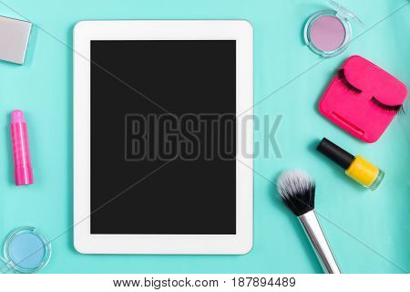 Order makeup online, tablet with copy space. Female essentials, everyday make-up. Flat lay of cosmetics on bright blue background, objects