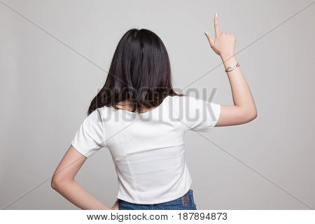 Back Of Asian Woman Touching The Screen With Her Finger.