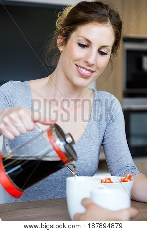 Portrait of beautiful young woman serving coffee on a cup in the kitchen at home.
