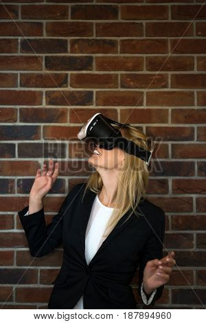 Woman in VR headset looking up and trying to touch objects in virtual reality.
