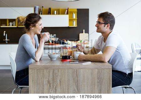 Portrait of beautiful young couple enjoying breakfast in the kitchen at home.
