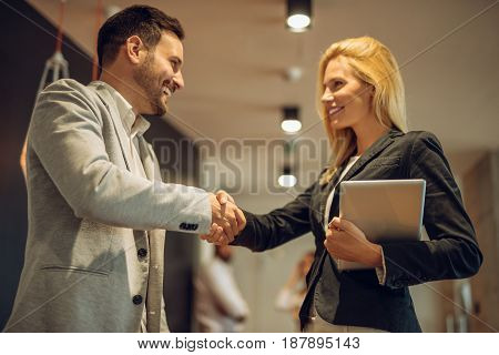 Two successful business people handshaking in the office.