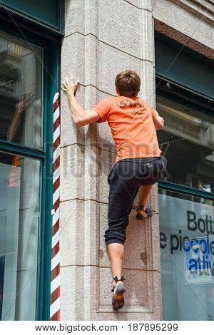 Man Climbing A House Wall On Street Boulder Contest