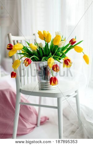 Tulips Over A White And French Wood Chair.