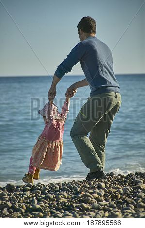 Father and daughter intent on playing together and lovingly on the shore of the sea. Children's memories and memories