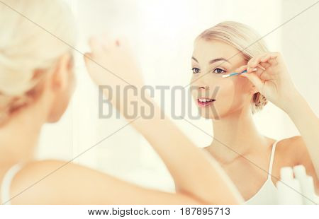 beauty, hygiene and people concept - smiling young woman fixing makeup with cotton swab and looking to mirror at home bathroom