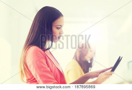 business, technology, startup and people concept - creative african woman with tablet pc at office