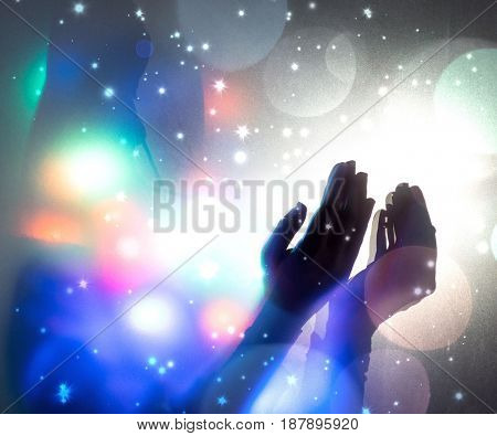 Hands praying in dark room with nice lights around her