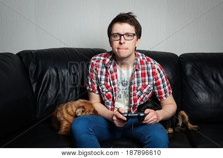 The Young Man In The Red Shirt And Glasses Playing Video Games With A Joystick Sitting On A Black Le