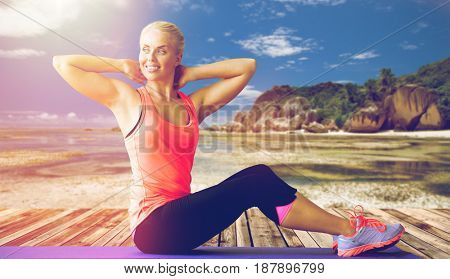 fitness, sport, training and people concept - smiling woman exercising on mat outdoors over exotic tropical beach background