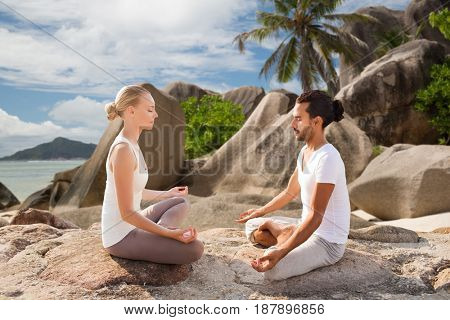 fitness, sport, meditation and people concept - happy couple doing yoga and meditating outdoors over tropical natural background