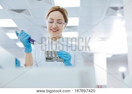 Work and smile. Competent medical worker expressing positivity while working in the modern laboratory