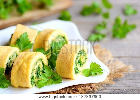 Home cheese and parsley stuffed omelet rolls on a plate. Cut fried omelet with grated cheese and finely chopped parsley. Tasty and gluten free breakfast omelet idea. Rustic style
