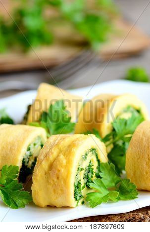 Homemade cheese and parsley stuffed omelette rolls. Cut fried omelette with grated cheese and finely chopped herbs. Delicious and gluten free breakfast omelette recipe. Rustic style. Closeup