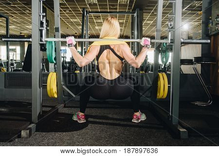 Back view young adult girl doing heavy squat in gym with barbell. Woman with perfect abs doing squat exercises. Blonde fit woman in great shape. Fitness