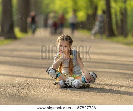 teen girl skating, sitting on asphalt and resting