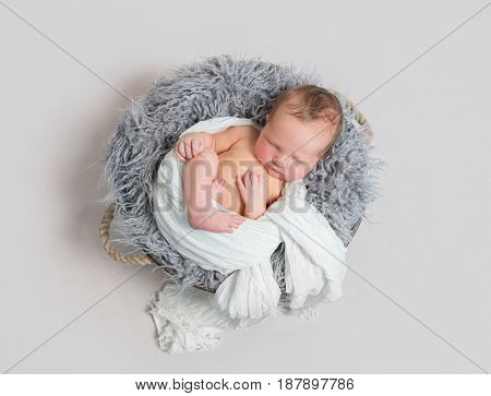 baby sleeping half wrapped up with white scarf