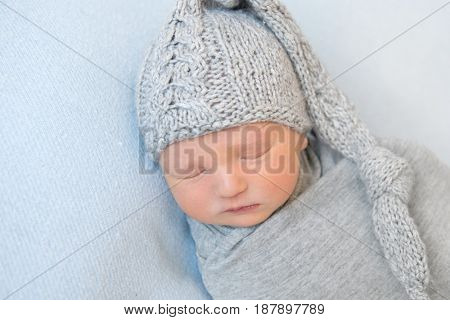 Adorable baby with knitted gray hat, napping
