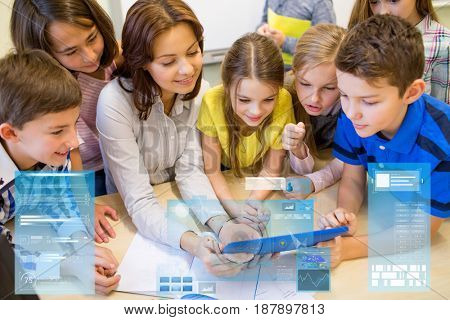 education, elementary school, learning, technology and people concept - group of kids with teacher looking to tablet pc computer in classroom over virtual screens projections