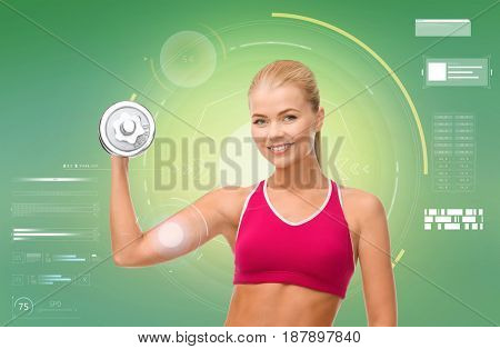 sport, fitness, exercising, technology and people concept - happy young sporty woman with dumbbell flexing biceps over green background