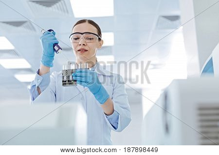 Close your mouth. Delighted scientist holding medicine dropper in right hand and glass holder in left hand while looking downwards