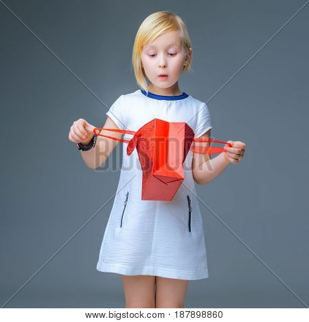 Surprised Child On Grey Looking In Red Christmas Shopping Bag