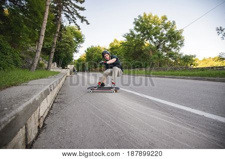 A young man in a helmet and protective gloves makes a slide on a longboard in the resort area of the city