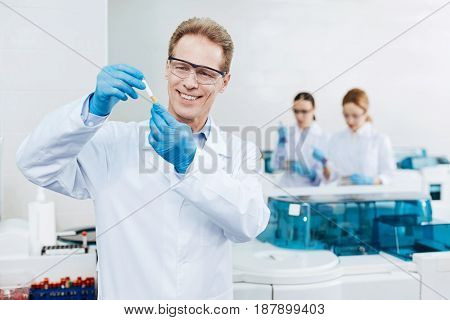 Be very careful. Positive delighted practitioner wearing protective glasses raising both hands while checking test tube