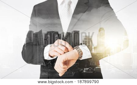 people, business and time concept - close up of businessman with wristwatch over city with double exposure