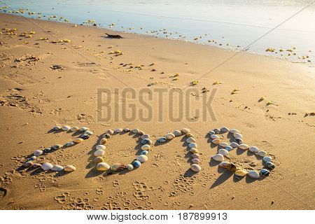 2018 New Year text made using shells on sand at Glenelg beach