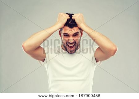 emotions, stress, madness and people concept - crazy shouting man rending ones hair in t-shirt over gray background
