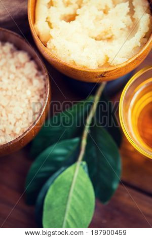 beauty, spa, body care, natural cosmetics and wellness concept - close up of body scrub in wooden bowl
