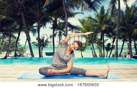 fitness, sport, people and healthy lifestyle concept - happy woman making yoga and stretching on mat over hotel resort pool on tropical beach background