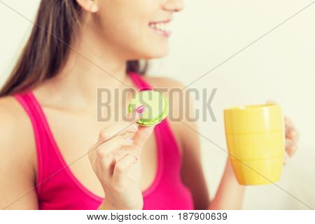 friendship, people, pajama party and junk food concept - close up of happy woman or teen girl with tea cup eating macaroon cookie at home