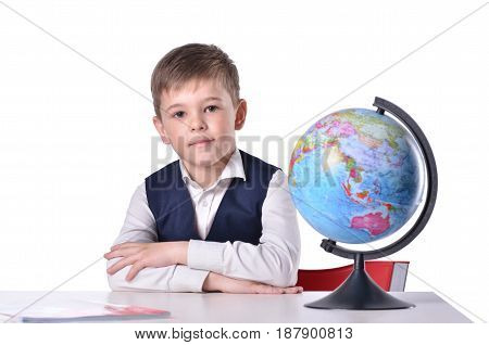 Schoolboy at the desk with a globe on it isolated on white background
