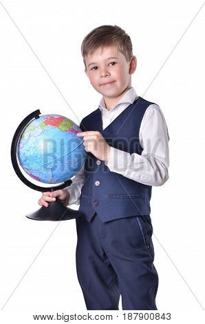 Standing schoolboy hold a globe of world and pointing on it isolated on white background
