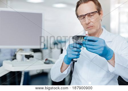 Protecting glass. Competent medical worker pressing lips while looking forward and checking blood