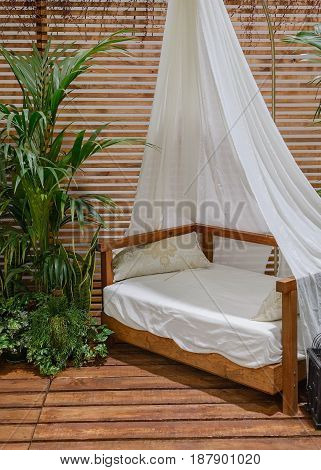 image of four-poster bed on a wooden porch