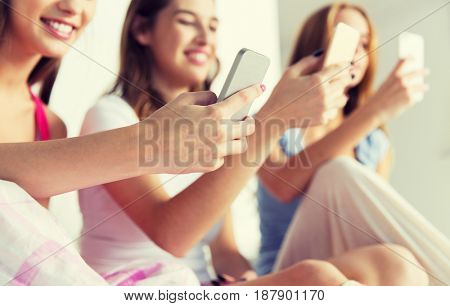 friendship, people, pajama party and technology concept - close up of happy friends or teenage girls with smartphones at home