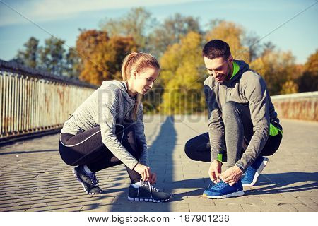 fitness, sport, training, people and lifestyle concept - smiling couple tying shoelaces of sneakers outdoors