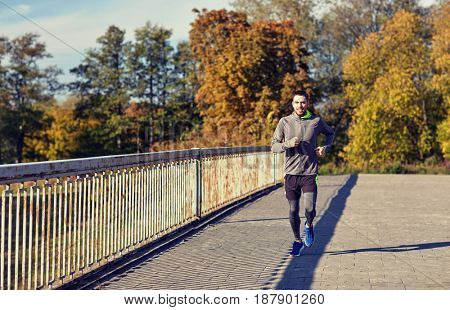 fitness, sport, people and lifestyle concept - happy young man running over city bridge